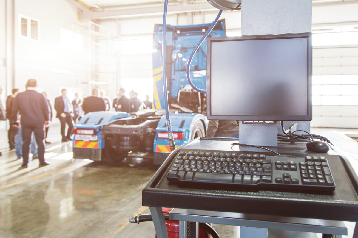 Service Garage with Computer in Foreground, Heavy Duty Truck and Service Staff in Background